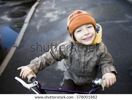 little cute boy on bicycle smiling close up outside spring in city - stock photo