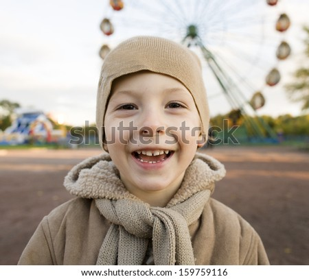 little cute boy outside in park near carousel