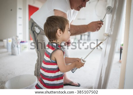 Little cute boy painting on a wall - stock photo