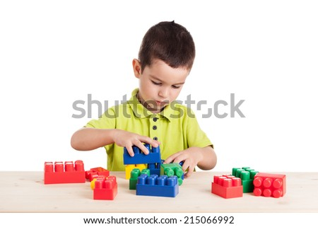 Little cute boy playing with colorful blocks. Isolated on white. - stock photo