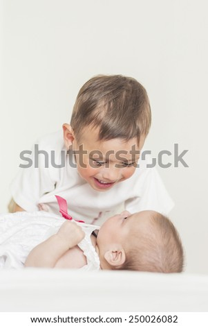 Little Cute Boy Playing with His Infant Sister and Smiling.Against White Background. Vertical Image Composition