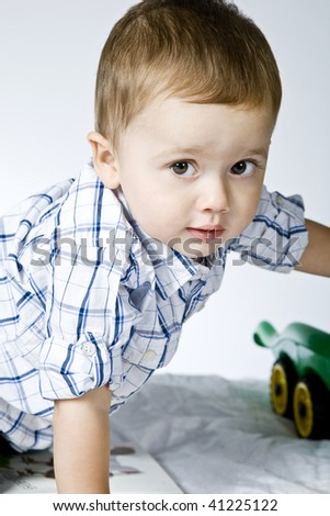 Little cute boy playing with toy car.