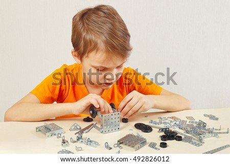 Little cute boy plays with mechanical starter kit at the table