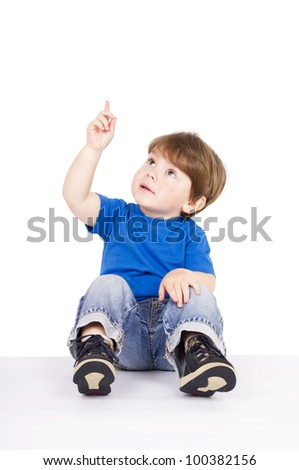 Little, cute boy pointing upwards with his finger.