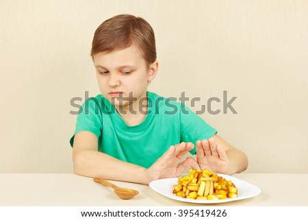 Little cute boy refuses to eat a fries - stock photo