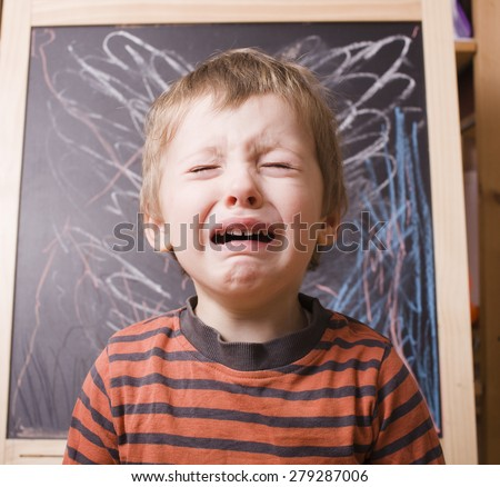 little cute boy screaming and crying at school near blackboard close up - stock photo