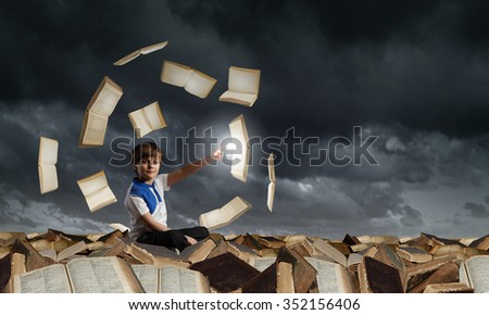 Little cute boy sitting on pile of books and pointing with finger  - stock photo