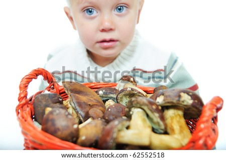 Little cute boy with a basket of mushrooms. Focus on the basket. In studio