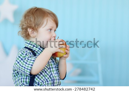 Little cute boy with curly hair bites red apple and dreams in blue room - stock photo