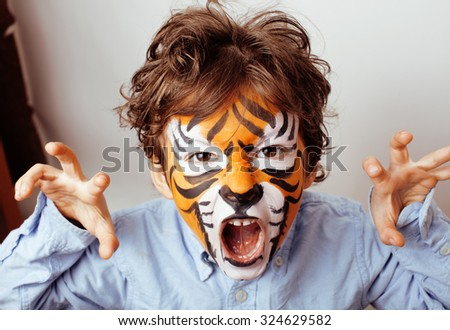 little cute boy with faceart on birthday party close up, little cute orange tiger - stock photo