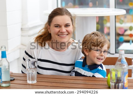 Little cute boy with glasses and his mother enjoying drinks in outside cafe in summer. Happy family having fun together. - stock photo