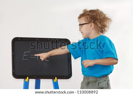 Little cute boy with glasses shows Einstein's formula on a blackboard