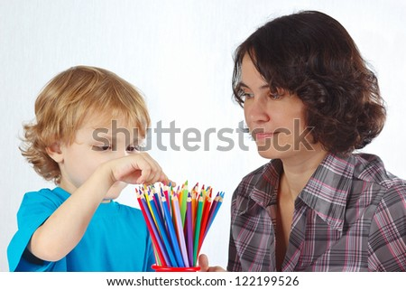 Little cute boy with his mother looks on color pencils on a white background - stock photo