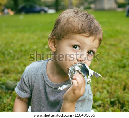 little cute boy with ice cream outside