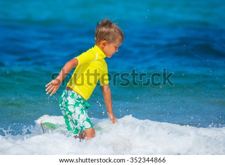 Little cute boy with learning surfing in the sea - stock photo