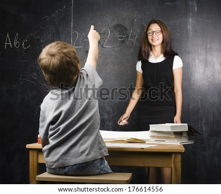 little cute boy with teacher in classroom at blackboard - stock photo