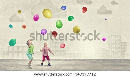Little cute boys playing joyfully with colorful balloon - stock photo