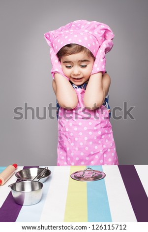 little cute chef shocked when she saw empty pots on the table - stock photo