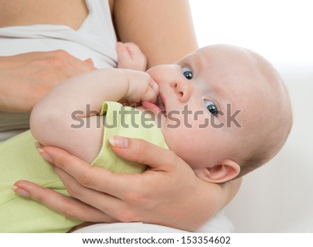 Little cute child baby girl on mother hands smiling and looking at the camera on a white background