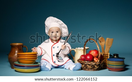 little cute cook with cutlery sitting on blue background - stock photo