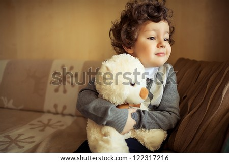 little cute curly  boy sitting at couch with teddy bear - stock photo
