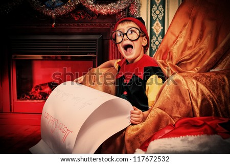Little cute elf boy is reading a letter to Santa Claus at home. - stock photo