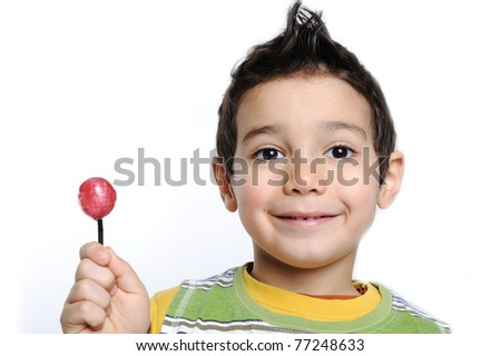 Little cute funny boy with colorful lollipop candy - stock photo