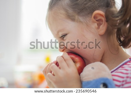 little cute girl biting red apple - stock photo