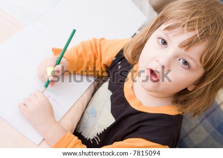 little, cute girl drawing with colorful crayons