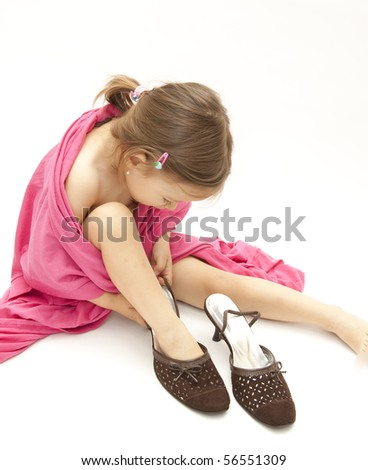 little cute girl dressing with her mother shoes and cloths - stock photo