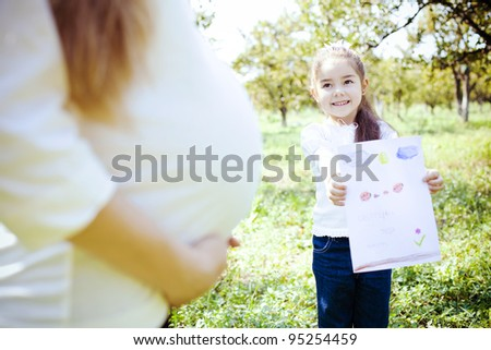 little cute girl, drew a picture for pregnant mothers as a gift - stock photo