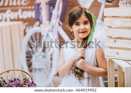 little cute girl embracing big white teddy bear indoors. Little kid near flower pot and bicycle.