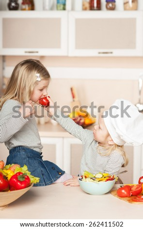 Little cute girl feeding her older sister tomato while helping their mother to cook salad. Kitchen interior. Concept for young kitchen hands - stock photo