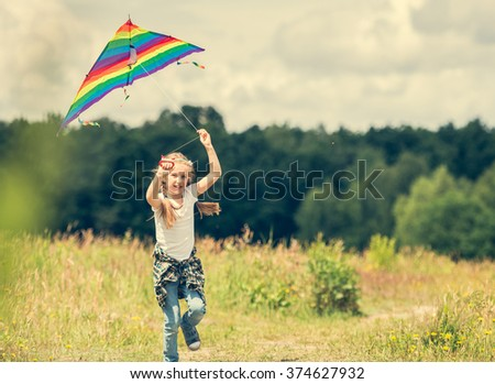 little cute girl flying a kite in a meadow on a sunny day - stock photo
