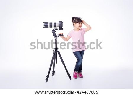 little cute girl holding a modern professional photo camera on tripod. child photographs - stock photo