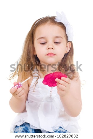 little cute girl holding  lipstick looking at the mirror on white background - stock photo