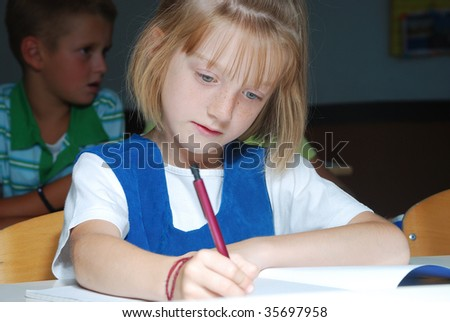 Little cute girl in classroom, writting