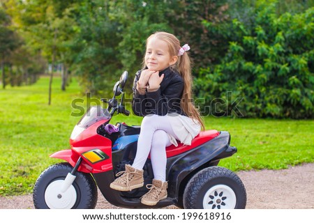 Little cute girl in leather jacket sitting on her toy motorcycle - stock photo