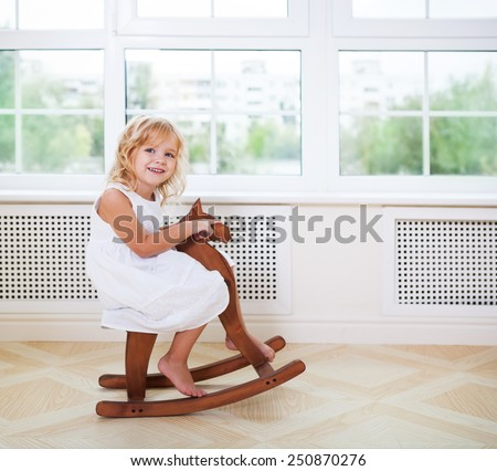 Little cute girl in nursery room with wooden horse near the window - stock photo