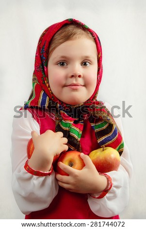 Little cute girl in Russian national clothes with apples. traditions - stock photo