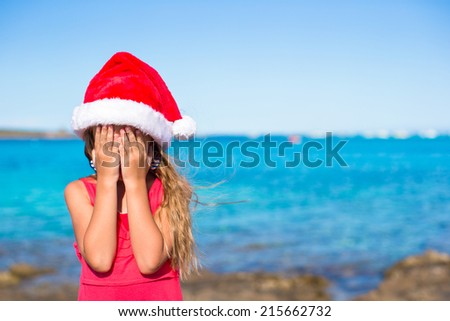 Little cute girl in santa hat covering her face background the sea - stock photo