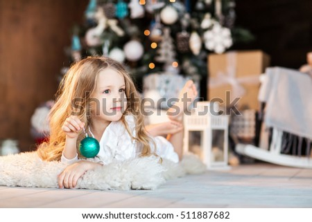 Little cute girl in santa hat near christmas tree