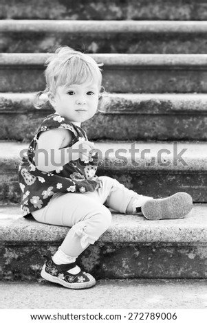Little cute girl in sitting on the stairs with stone steps ( black and white ) - stock photo