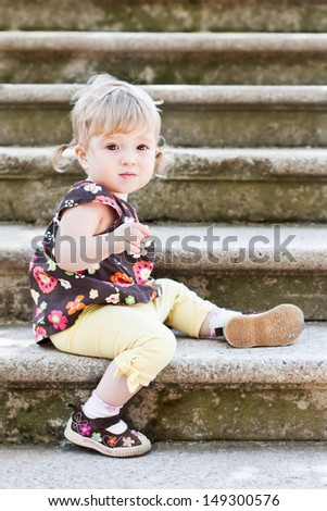 Little cute girl in sitting on the stairs with stone steps, selective focus on face - stock photo