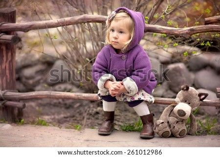 little cute girl in the purple coat with hood is sitting near the wooden fence with her toy wolf - stock photo