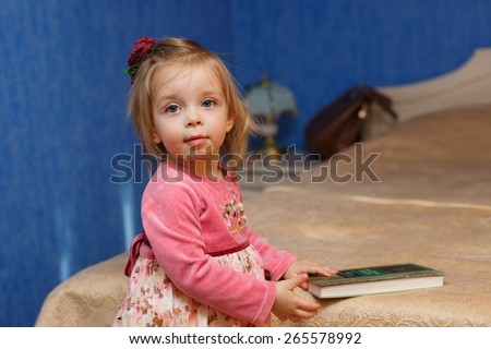 Little cute girl is going to read a book in the bedroom. The concept of education in the preschool years. - stock photo