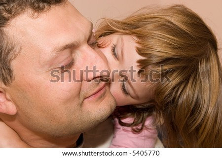 little, cute girl kissing her father