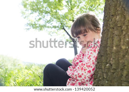 Little cute girl  leaning against a tree in the forest