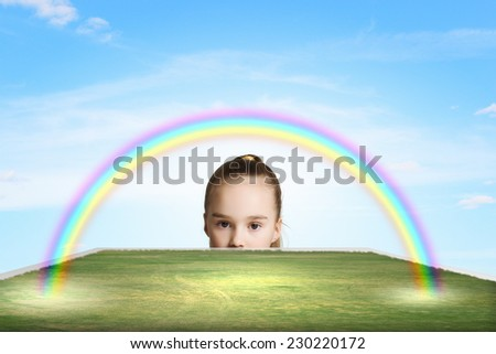 Little cute girl looking at colorful rainbow - stock photo