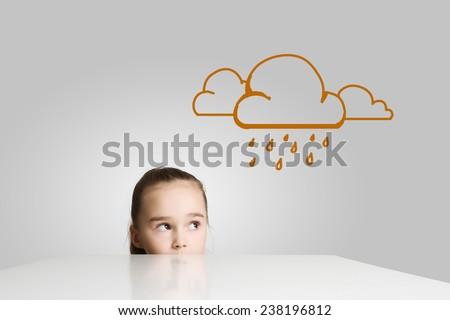 Little cute girl looking at raining cloud - stock photo